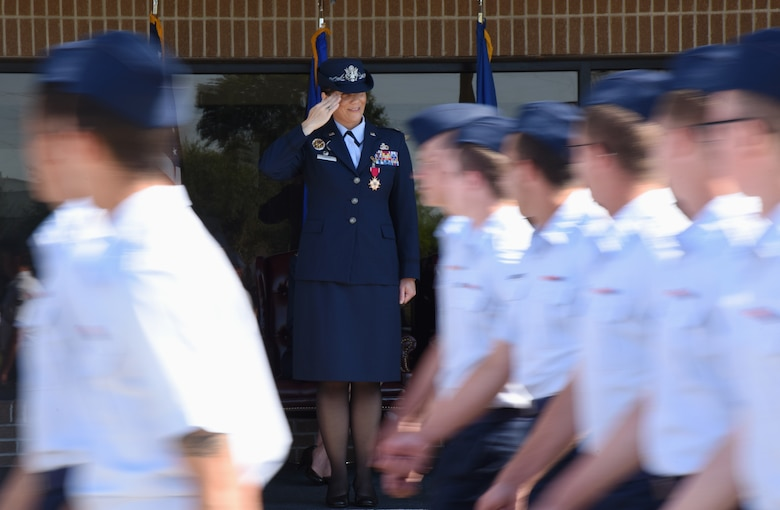 U.S. Air Force Col. Debra Lovette, outgoing 81st Training Wing commander, salutes Airmen as they march by during the change of command ceremony on the Levitow Training Support Facility drill pad at Keesler Air Force Base, Mississippi, May 16, 2019. The ceremony is a symbol of command being exchanged from one commander to the next by the handing-off of a ceremonial guidon. Lovette is now assigned to the U.S. Space Command. (U.S. Air Force photo by Kemberly Groue)