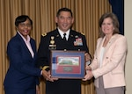 DLA EEO Deputy Director Angela Curtis (left) and DLA Chief of Staff Kristin French (right) present Army Maj. Gen. Garrett Yee with a framed photo of the McNamara Headquarters Complex. Photo by Teodora Mocanu.