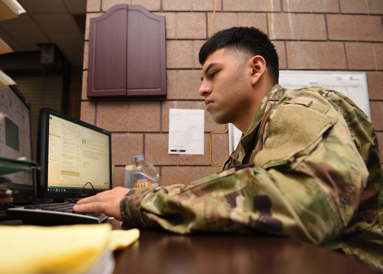 A man operates a laptop computer.