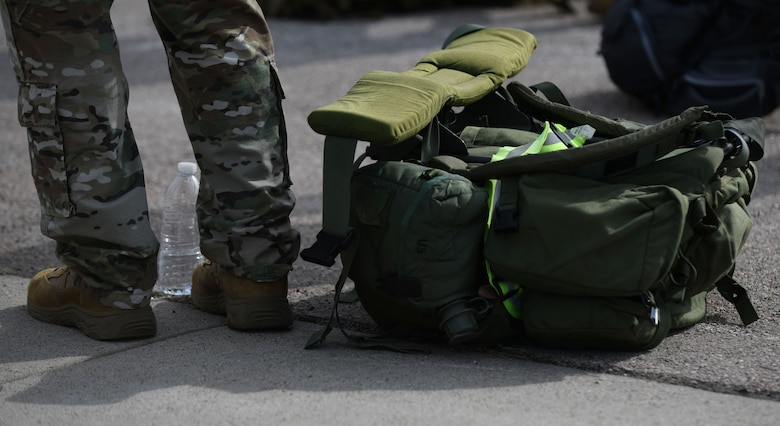 An Airman stands beside his rucksack as he waits for it to be weighed during the Police Week Ruck Challenge at Heritage Lake on Ellsworth Air Force Base, S.D., May 13, 2019. Participants had the option of filling their rucksacks with canned goods that were donated to Feeding South Dakota. Feeding South Dakota is an organization that provides food assistance to people throughout the state. (U.S. Air Force photo by Airman 1st Class Christina Bennett)