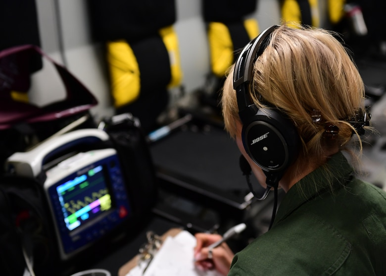 Staff Sgt. Lisa Zeng, medical technician with the 914th Aeromedical Evacuation Squadron, reads blood pressure readings over Honolulu, Hawaii April 24, 2019. The technicians had to use each other to practice as there were not any actual patients on board the plane for the training mission. (U.S. Air Force photo by Senior Airman Grace Thomson)