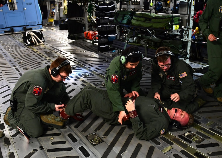 Staff Sgts. Raymond Johnson, John Klobushnik, and Scott Wardo, medical technicians with the 914th Aeromedical Evacuation Squadron, and Capt. Megan Taggert, 914th AES flight nurse, practice putting restraints on a mental health patient above Honolulu, Hawaii April 24, 2019. Johnson was playing the part of the mental health patient while Klobushnik, Wardo and Taggert practiced the restraint procedures. (U.S. Air Force photo by Senior Airman Grace Thomson)