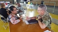 Col. Francisco J. Perez Rivera, a medical provider from the 49th Multifunctional Medical Battalion, U.S. Army Reserve-Puerto Rico, talks with patient Lydia Torres, at the Innovative Readiness Training site in Yauco, May 3, 2019. (Photo Credit: U.S. Army)