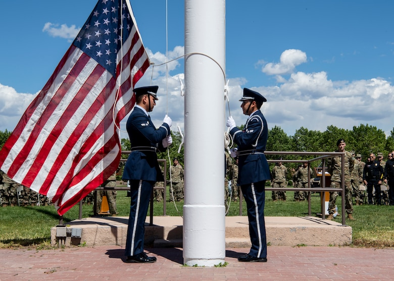Kirtland Air Force Base Honor Guardsmen prepare to hoist the flag after lowering it from half-staff during the Police Week Memorial Retreat Ceremony at Kirtland Air Force Base, N.M., May 15. When lowering the flag from half-staff, it must first be hoisted to the peak before being lowered. (U.S. Air Force photo by Staff Sgt. J.D. Strong II)