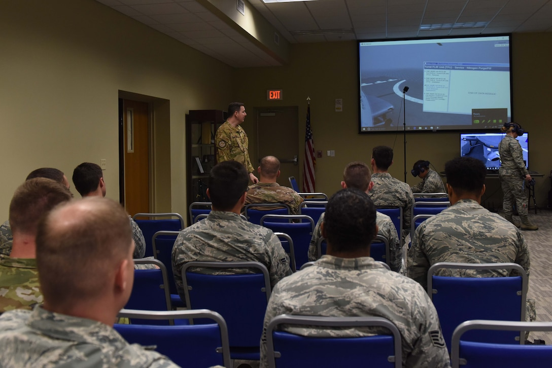 A man dressed in operational camouflage pattern speaks to a crowd of military service members in front of a large projected screen