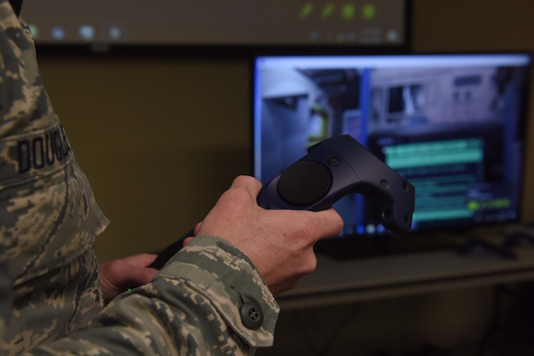 A closeup photo of someone wearing an Airman Battle Uniform holding a virtual reality controller