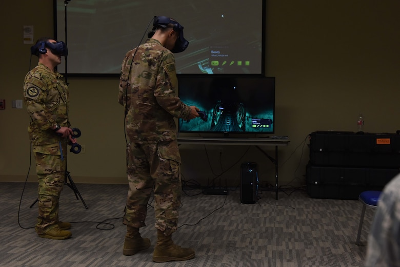 Two Airmen wearing occupational camouflage pattern uniform stand in front of a projector while using virtual reality gear