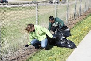 Cpl. Sierra Tryon of the Wyoming National Guard and member of Laramie County Community College's Student Veteran Association and Nicole Ng, Air and Water Program Manager for the 90th Missile Wing, clean a section of fence along the Cheyenne Greenway in Cheyenne, Wyo., May 11. More than fifty volunteers came out as part of the Crow Creek Revival project aimed at bringing the creek closer to its original state.
