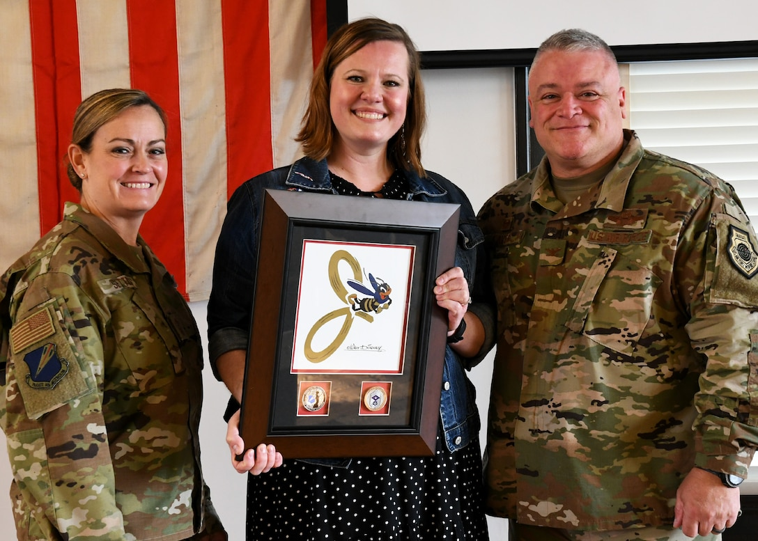 131st Bomb Wing commander Col. Ken Eaves and wing command Chief Master Sgt. Jessica Settle present Ms. Leah Winchester, grand daughter of Naomi Parker, a framed J-Bee.  The J-Bee was drawn in 1943 by famed cartoonist Walt Disney as the official insignia of Jefferson Barracks.