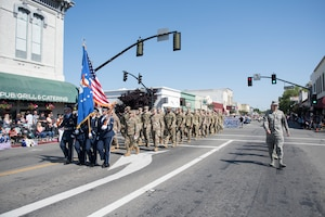 U.S. Air Force Airmen assigned to the 60th Air Mobility Wing, led by Col. Theresa Weems, 60th Operations Group commander, center, render a salute during the national anthem at the annual Dixon May Fair Parade in Dixon, California, May 11, 2019. The Airmen, from the 60th Operations Group and the Wing Staff Agency, marched in the parade to promote community engagement and build strong partnerships. (U.S. Air Force photo by Airman 1st Class Amy Younger)