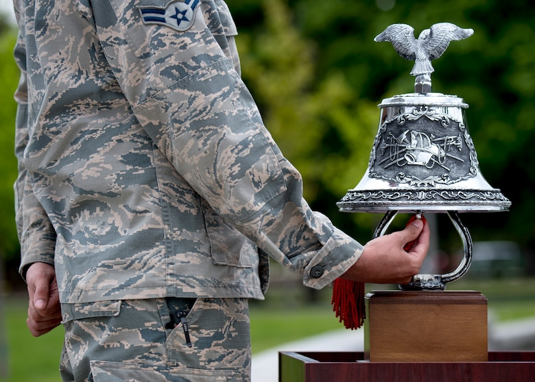 U.S. Air Force Airman 1st Class Ponce Francisco, 92nd Security Forces Squadron installation entry controller, rings a bell in remembrance of fallen law enforcement officers during a National Police Week Memorial Retreat Ceremony at Fairchild Air Force Base, Washington, May 15, 2019. The law enforcement community is honored annually with numerous events after President John F. Kennedy signed a proclamation in 1962 to designate May 15 as Peace Officers Memorial Day and the week as National Police Week. (U.S. Air Force photo by Airman 1st Class Whitney Laine)