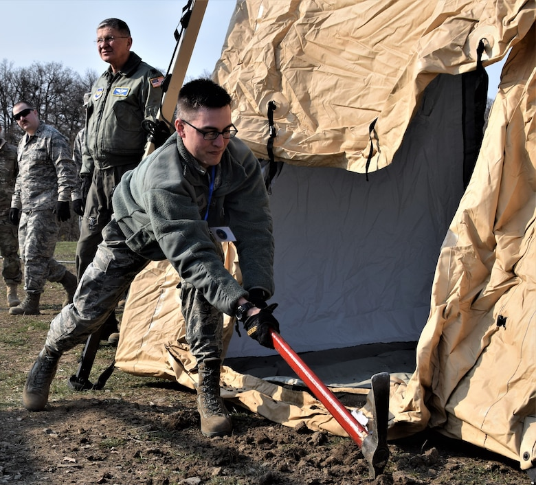 Tech. Sgt. Christopher Sarchioto, 86th Medical Group, Ramstein Air Base Germany, prepares an expeditionary medical support system (EMEDS) at Cincu Military Base, Romania, April 4, 2019, during exercise Vigorous Warrior 19. EMEDS are modular field hospitals designed to be deployed and fully operational within six hours of arrival in an area of responsibility. (U.S. Air Force photo illustration)