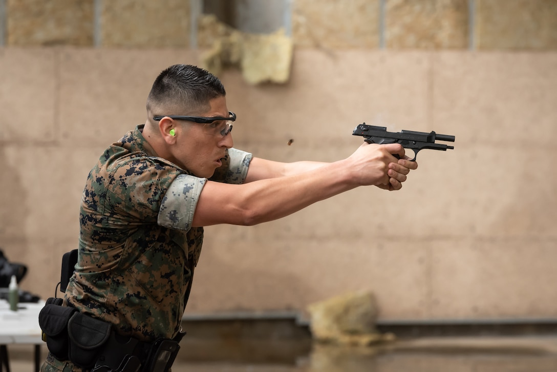 A U.S. Marine assigned to the Provost Marshal Office, fires an M9 pistol during a stress fire competition May 17, 2019, at Kadena Air Base, Japan.