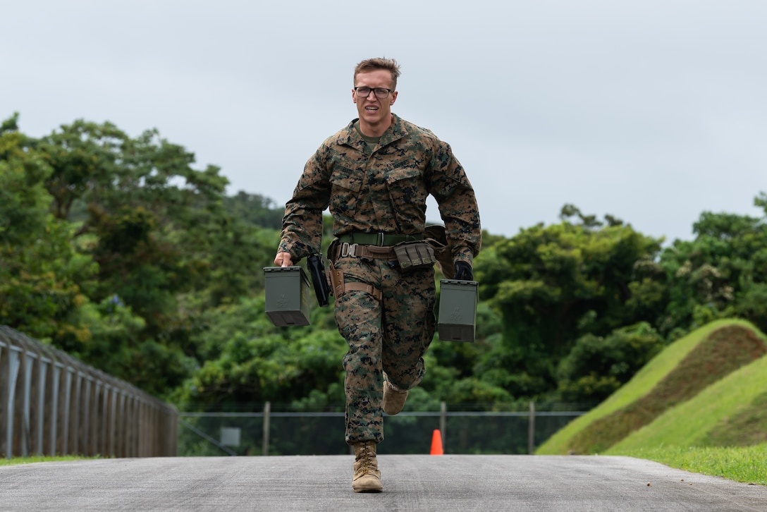 A U.S. Marine assigned to the Provost Marshal Office, carries ammo cans during a stress fire competition May 17, 2019, at Kadena Air Base, Japan.