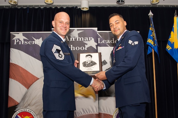 U.S. Air Force Chief Master Sgt. Christopher Ostrom, 52nd Civil Engineer Squadron fire chief, left, presents the John L. Levitow award to Senior Airman Justin Gray, 52nd Operations Support Squadron air traffic controller, right, during the Pitsenbarger Airman Leadership School 19-D graduation in Club Eifel at Spangdahlem Air Base, Germany, May 16, 2019. The Levitow award is the highest honor given to the student who displays excellence in all categories of ALS. (U.S. Air Force photo by Airman 1st Class Valerie Seelye)