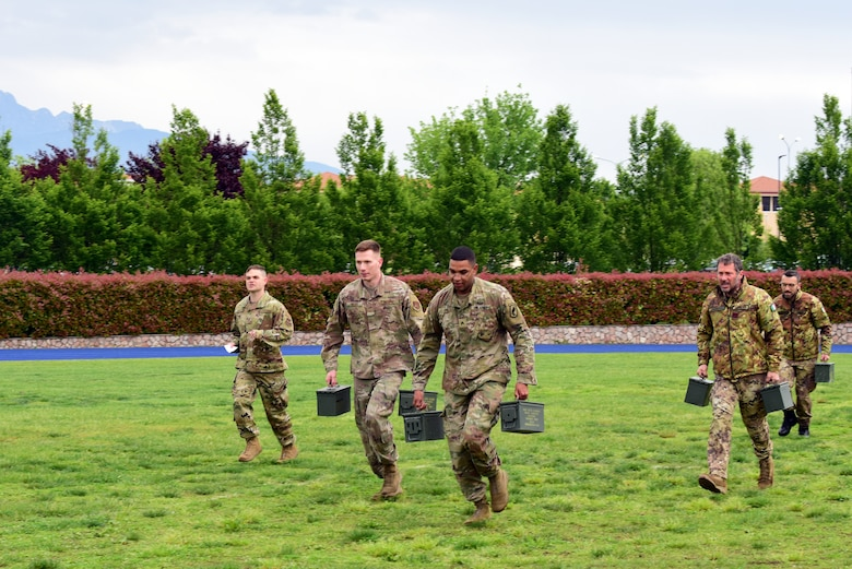 U.S. Air Force and Army members and Italian Air Force members carry ammo cans as they run to the next task during the Police Week Combat Challenge that pit security forces Airmen against Joint International Non Commissioned Officer Development Course held May 15, 2019 at Aviano Air Base, Italy. The combat challenge was a friendly competition to promote teamwork among the service members. (U.S. Air Force photo by Airman 1st Class Caleb House)