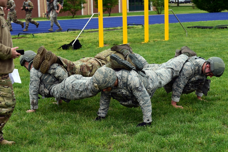 31st Security Forces Squadron Airmen engage in a square pushup to build teamwork during the Police Week Combat Challenge held May 15, 2019 at Aviano Air Base, Italy. The combat challenge was the first event of the 2019 Joint International Non Commissioned Officer course Development Course. (U.S. Air Force photo by Airman 1st Class Caleb House)
