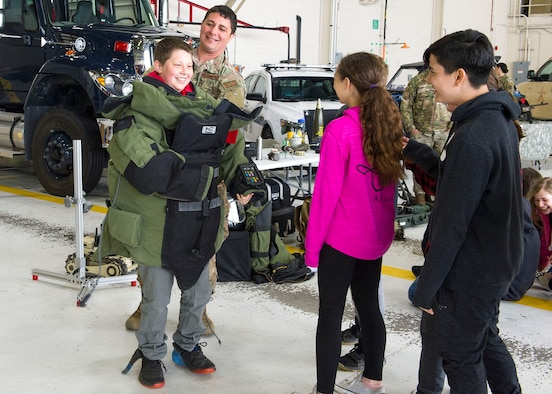 Staff Sgt. Trenton Hawk, a 434th Civil Engineer Squadron technician, helps a student try on a bomb suit during a police week event at Grissom Air Reserve Base, Ind., May 13, 2019. Students from area schools visited the base and participated in briefings and demonstrations from various law enforcement agencies throughout the state.  (U.S. Air Force photo by Staff Sgt. Courtney Dotson-Essett)