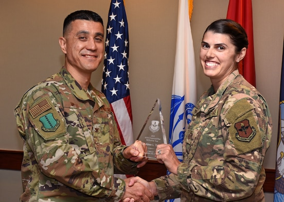 Col. Ricky Mills, 17th Training Wing Commander, presents the Air Education and Training Command Command Post Noncommissioned Officer the Year award to Tech. Sgt. Aimee Thomas, 17th Training Wing CP Command and Control Operations NCO in charge, at Goodfellow Air Force Base, Texas, May 14, 2019. It's the job of Command Post specialists to ensure operations and communications run efficiently and effectively under any circumstance. (U.S. Air Force photo by Senior Airman Seraiah Hines)