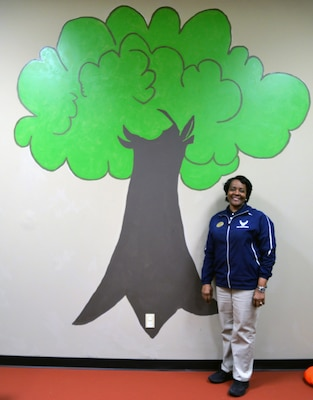Feletia McLaurin, Medical Education and Training Campus Fitness Center fitness and sports manager, stands beside a mural of a tree she painted in the new Parent Child Area at the fitness that officially opens June 3. Located in a former workout room and storage space at the fitness center, the Parent Child Area has a play area and small table for children and includes a flat screen TV and DVD player for viewing children's movies. In addition, it includes an area with new exercise equipment for parents to work out on while they watch over their children.