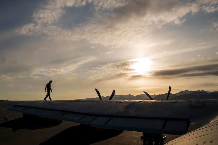A silhouette of a man as he walks along the wing of a plane at twilight.