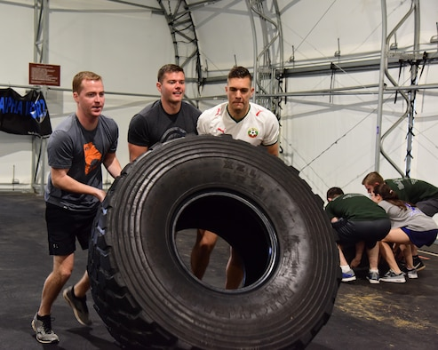 """Team members flip a tire during the A-BLAZIN' Race May 10, 2019, on Columbus Air Force Base, Miss. Similar to the challenges in the international game show, the """"Amazing Race"""", teams raced against each other in a competition to see who could complete the stationed challenges in the shortest amount of time. (U.S. Air Force photo by Elizabeth Owens)"""