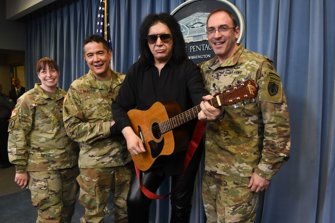 Famous musician Gene Simmons holds a guitar while standing next to three service members on the stage in the pentagon briefing room.