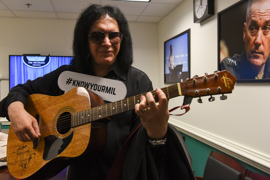 Famous musician Gene Simmons strums a guitar while wearing a #KNOWYOURMIL sign on his chest.