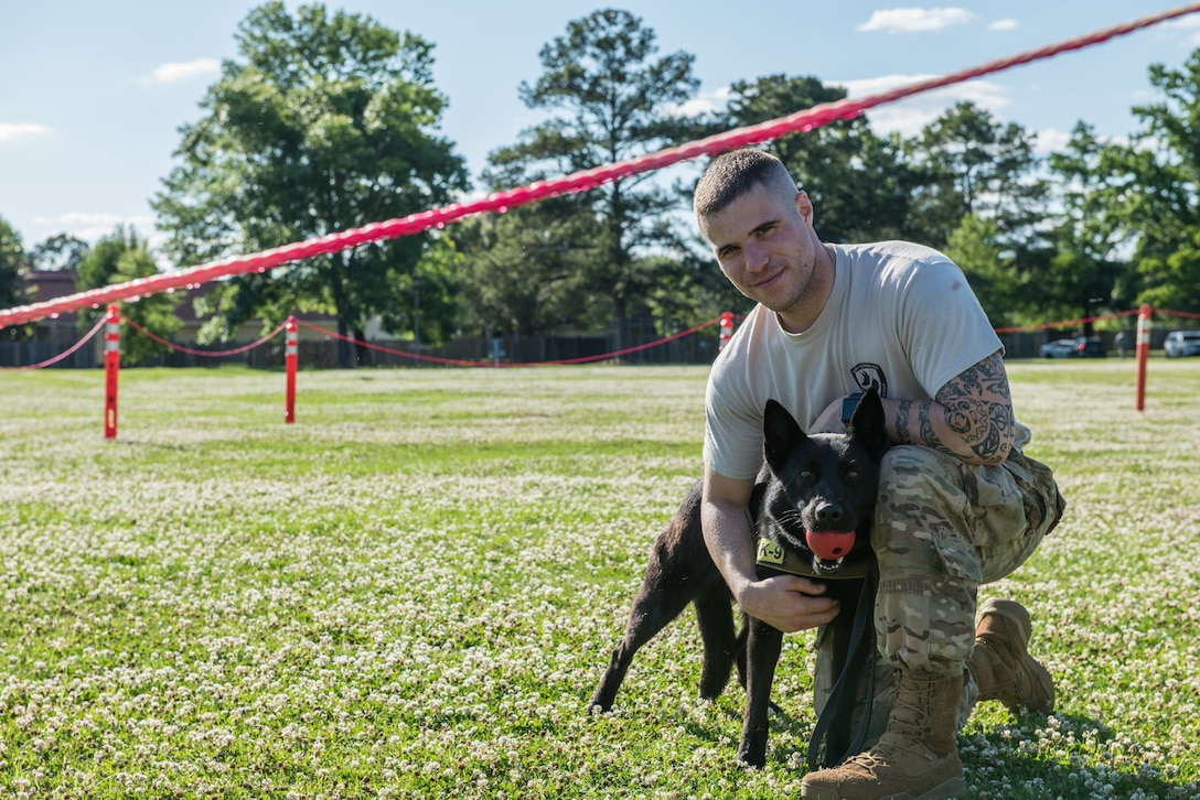 42nd Security Forces Squadron Airmen poses for a photo with a military working dog at Freedom Park.
