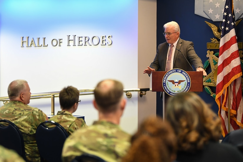 A man stands behind a lectern while speaking. An American flag is to his left.