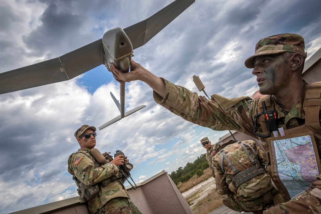 A crouching soldier with his face in camouflage holds a winged drone aloft and checks its underside as other soldiers look on.