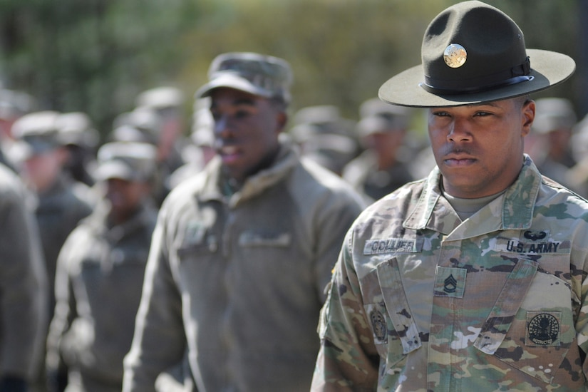 A drill sergeant stands in front of a formation.