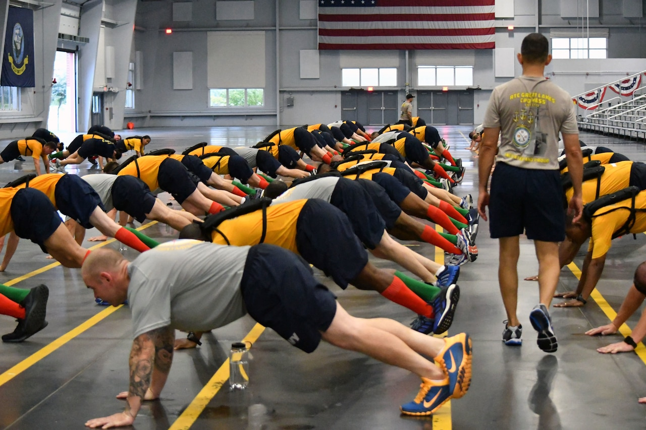 Sailors do pushups in a training bay.