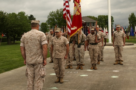 military formation for a retirement with color guard in the background.