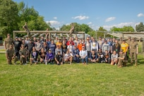 Coaches attending Marine Corps Recruiting Command's 2019 Coaches Workshop pose for a group photo with Marines during the Coaches Workshop aboard Marine Corps Base Quantico, Virginia, May 16, 2019. The Coaches Workshop educates approximately 50 collegiate coaches from across the nation about essential Marine Corps leadership skills and programs that they can share with their student athletes based on first-hand experiences. (U.S. Marine Corps photo by Lance Cpl. Mitchell Collyer)