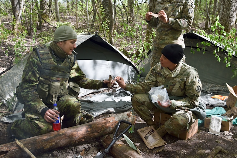 A member of the Estonian Defense Force shares a meal-ready-to-eat (MRE) with U.S. Army Spc. Angelique Helkowski, 290th Military Police Company, Maryland National Guard, May 6, 2019, in Ida-Viru County, Estonia. The Spring Storm exercise fostered collaboration for over 9,000 military personnel from more than a dozen NATO partner countries. (U.S. Air National Guard photo by Staff Sgt. Enjoli Saunders)