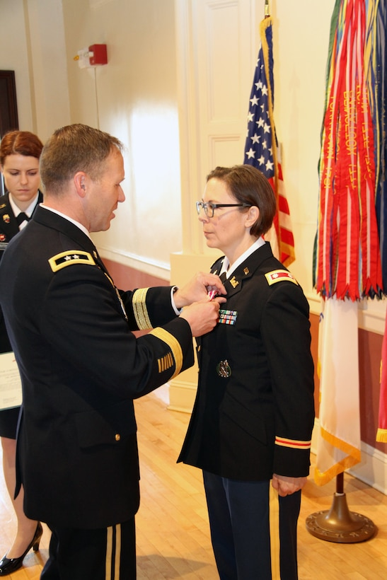 U.S. Army Corps of Engineers North Atlantic Division Commander Maj. Gen. Jeffrey Milhorn presents Lt. Col. Julie D'Annunzio with the Meritorious Service Medal during her retirement ceremony held May 10, at the Fort Hamilton Community Club's Washington Room in Brooklyn, New York.