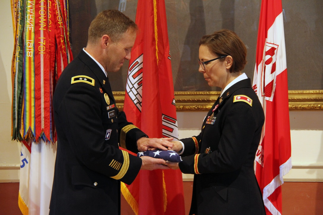 Lt. Col. Julie D'Annunzio (right) receives the traditional United States flag given to Army military retirees at the conclusion of their careers.