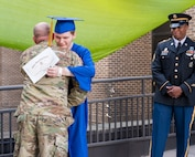 Army Future Soldier Justin Dees shares an embrace with Army recruiter Staff Sgt. Cory Barnes after receiving his diploma from William Blount High School. (Photo Credit: East Tennessee Childrens Hospital)