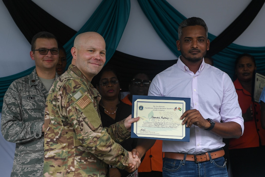 U.S. Air Force Lt. Col. Sean McNamara, Air Force Office of the Surgeon General, Falls Church, Virginia, presents Dr. Devendra Radhy, Port Mourant Hospital doctor in charge, with a certificate of appreciation during the closing ceremony of the ophthalmology center during New Horizons exercise 2019 at Port Mourant, Guyana, May 16, 2019. The ophthalmology clinic was established to provide aid to the Guyanese population by screening and selecting patients to receive cataract surgery in support of New Horizons 2019. The New Horizons exercise 2019 provides U.S. military members an opportunity to train for an overseas deployment and the logistical requirements it entails. The exercise promotes bilateral cooperation by providing opportunities for U.S. and partner nation military engineers, medical personnel and support staff to work and train side by side.(U.S. Air Force photo by Senior Airman Derek Seifert)