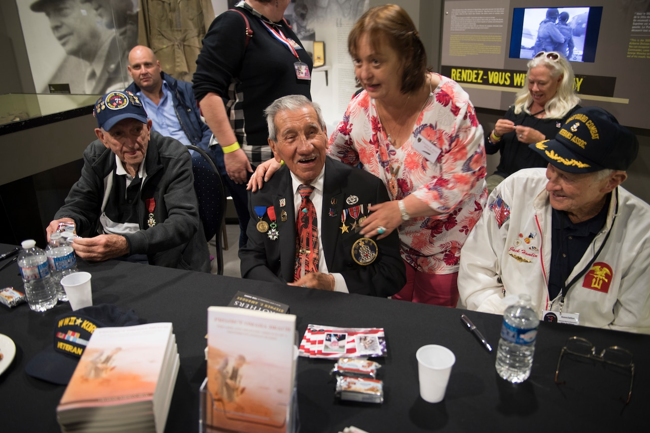 WWII veterans talk to a crowd.