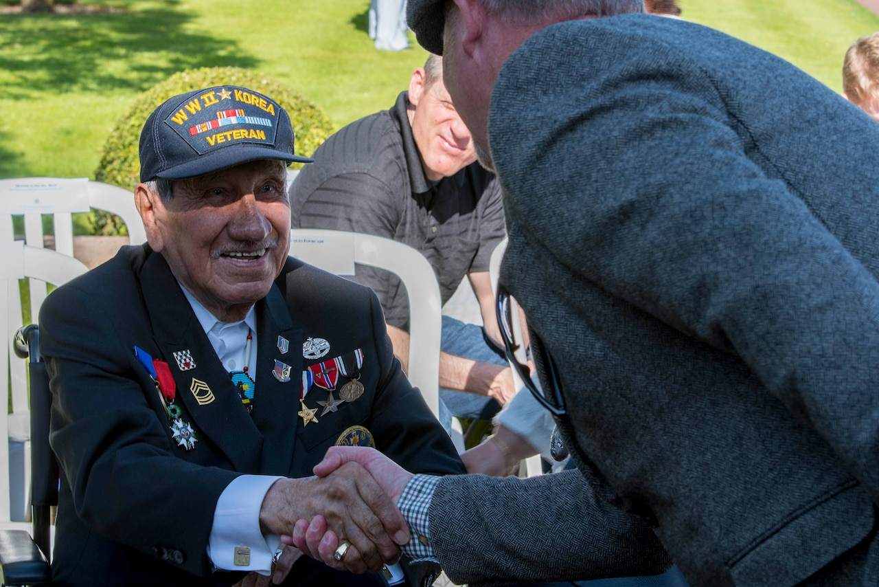 WWII veteran shakes hands with guests.