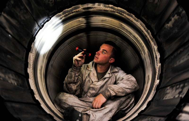 An airman holds a flashlight as he inspects the inside of a military jet.