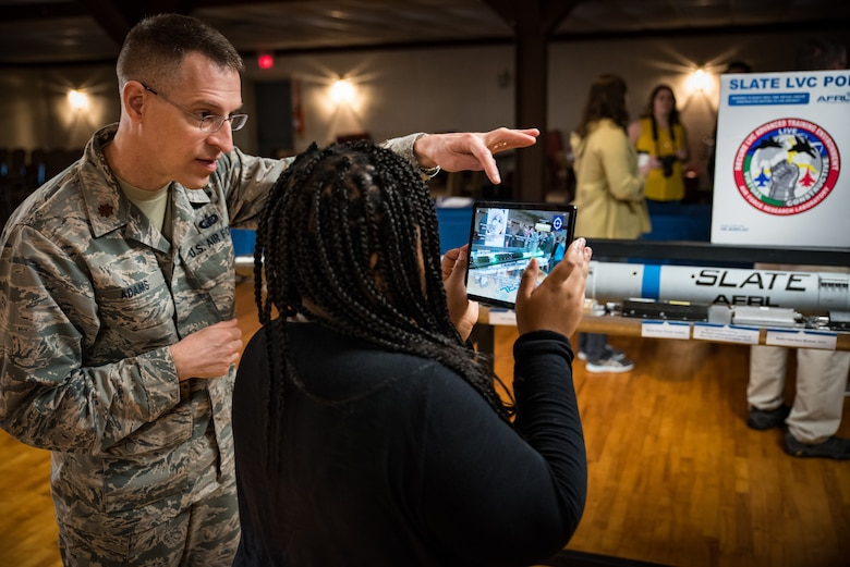 Using augmented reality and a tablet, Maj. Thomas Adams shows a participant how the components of the SLATE pod communicate with a live pilot to enhance live, virtual and constructive training during the Air Force Research Laboratory's 7th annual Full Throttle STEM at Eldora Speedway May 14. (U.S. Air Force photo/Richard Eldridge)