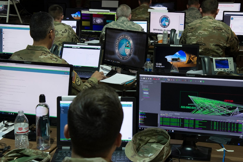 Service members sit at computer screens.