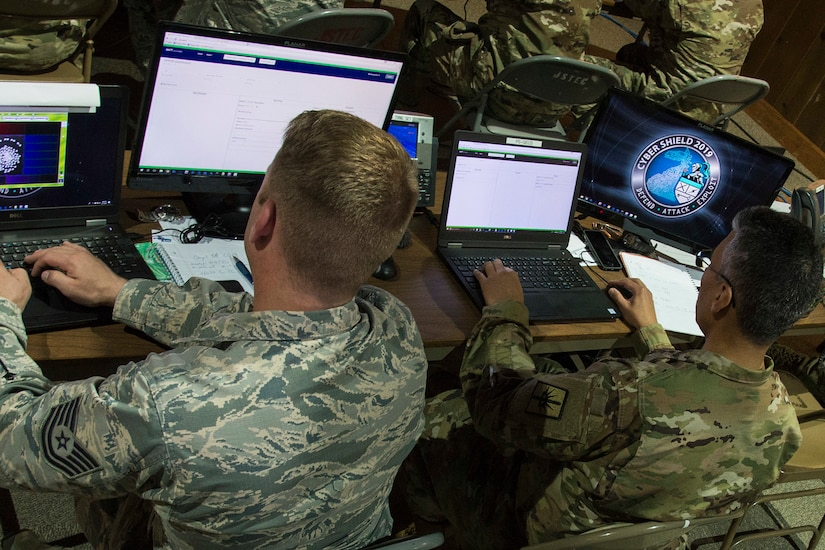 Two service members sit at a table with four computers.