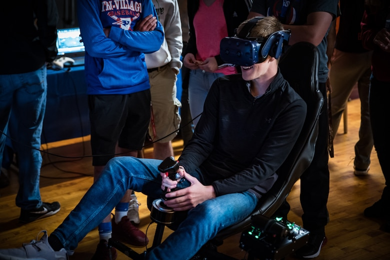 A student operates a jet simulator using virtual reality during the Air Force Research Laboratory's 7th annual Full Throttle STEM at Eldora Speedway May 14. (U.S. Air Force photo/Richard Eldridge)