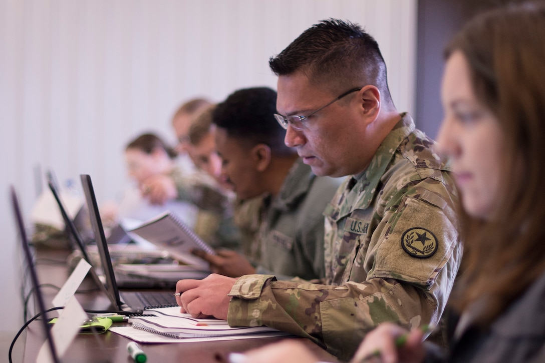 Service members and civilians sit at computers.
