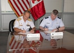 Military officers sign an agreement