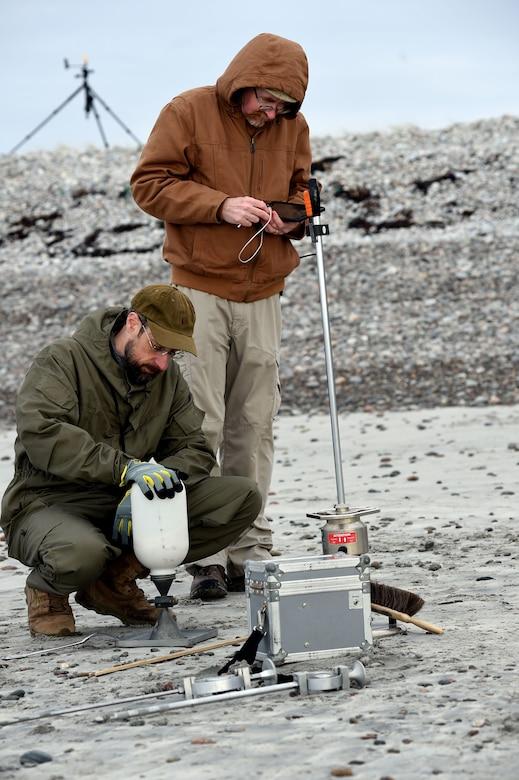 Two men hook up a device on a barren landscape.